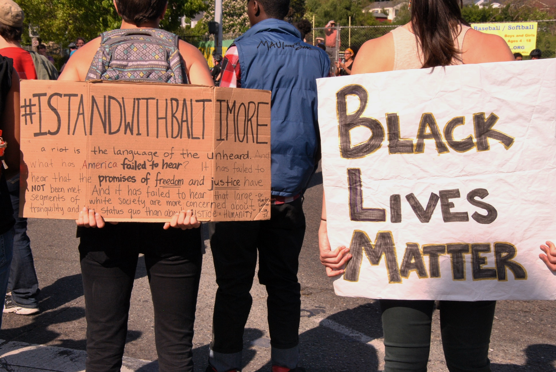 Demonstrators display signs showing solidarity with the city of Balitmore and the Black Lives Matter campaign. Photo Credit: Celia Berk