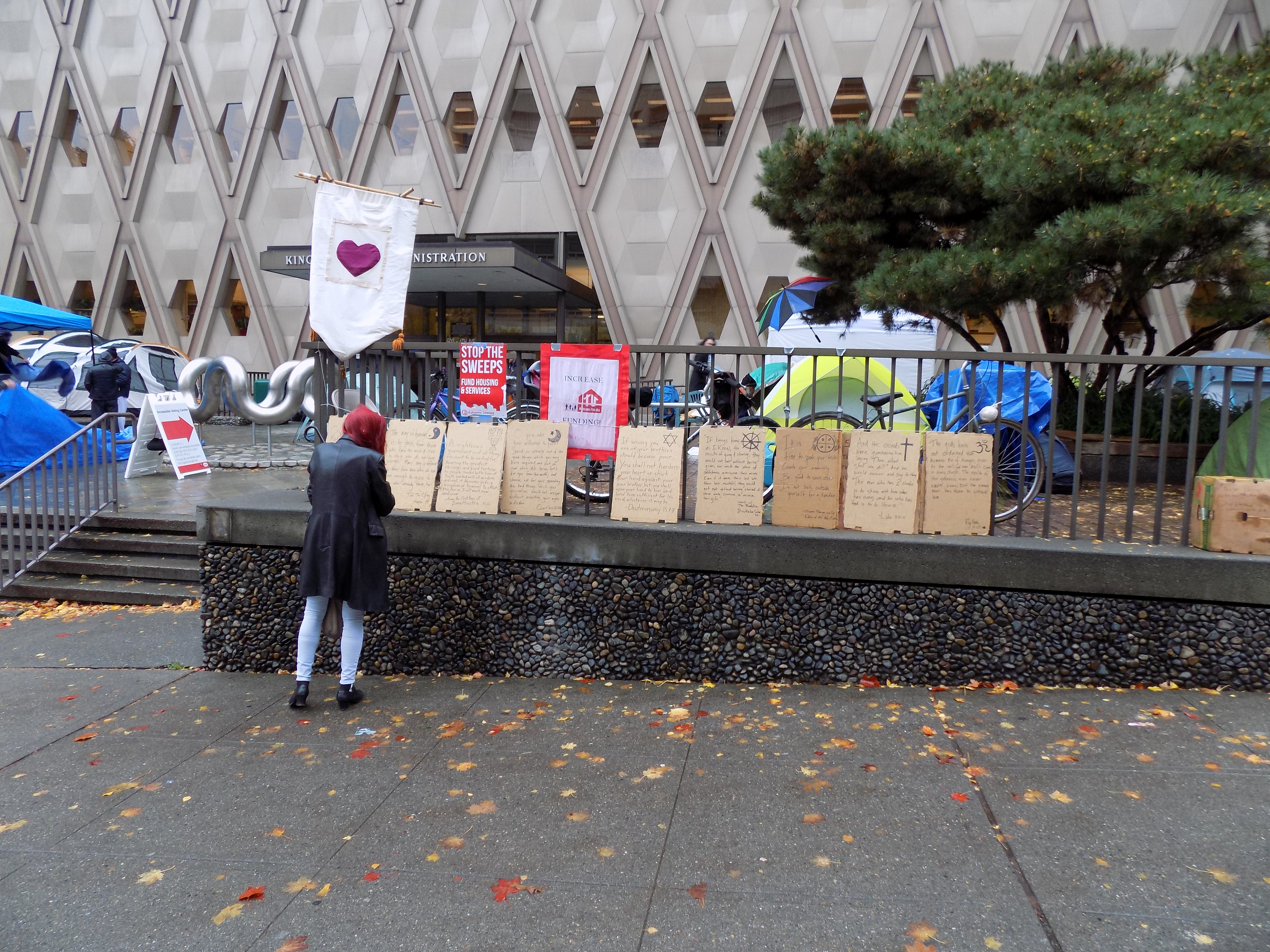 Image 3 Caption--A pedestrian examines a display at the camp erected by Occupy Chaplains.