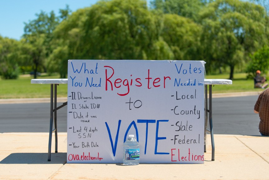 """White hand-made poster board sign with the words """"Register to Vote"""" written on it leans against a folding table on a sidewalk. The sign has other information written on it about registering to vote and voting."""